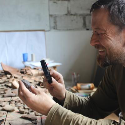 An archaeologist closely examines an artefact during one of our Archaeology opportunities abroad in Peru.